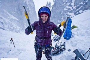 A climber smiles and shows off her hiking gear while snow ightly falls around her