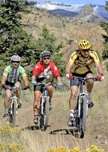 Three individuals trail bike riding