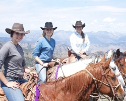 Three women on horseback with mountains in the background