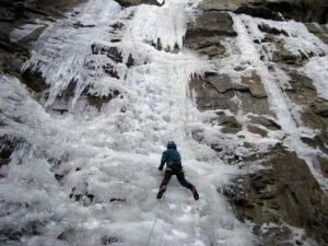 An individual climbs up a giant icy cliff