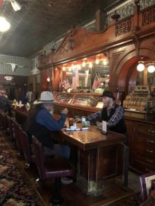 Men sit at the bar at the Irma Hotel