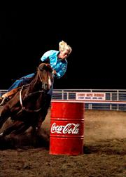 A rider takes their horse around a barrel course at the Cody Nite Rodeo