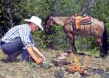 A man builds a fire at camp with a horse in the background