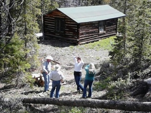 A group on a tour of a quaint log cabin