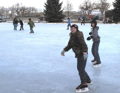 Teens ice skating on an outdoor rink