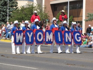 Individuals walking in the Cody Stampede Parade holding a Wyoming banner