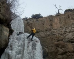 An ice climber scales the side of a cliff