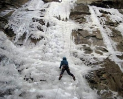 An ice climber climbs the side of a cliff