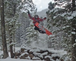 A snowboarder goes over a jump in perfect snow conditions