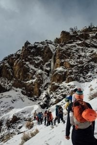 A group on climbers making their way through a snoy trail