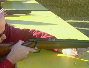A man aims a rifle at a target