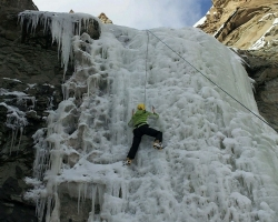 person ice climbs waterfall