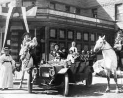 An archive photo of people in a car and on horseback in Cody, Wyoming