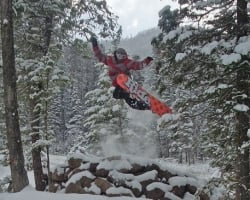 A snowboarder launching from a jump on a snowy hill