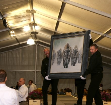 two men hold a painting of bison at an art sale