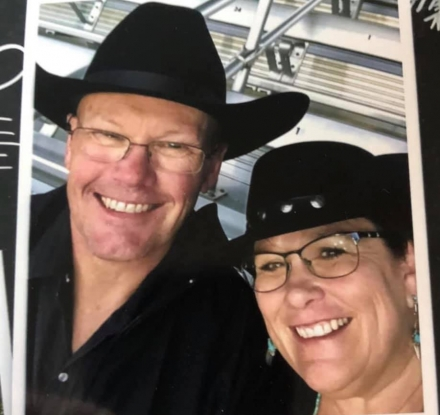 A couple taking a selfie wearing cowboy hats