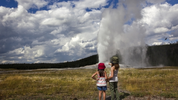 Backshot of two girls watching the Old Faithful as it erupts
