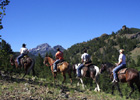 4 horseback riders with mountains