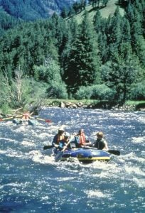 A group of paddlers enjoy an exciting whitewater raft ride in Cody/Yellowstone Country.