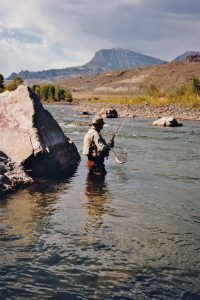 A fisherman casts a line in a river in Cody/Yellowstone Country.