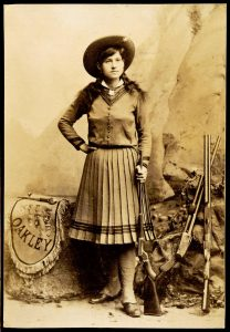 Sharpshooter Annie Oakley poses with her gun.