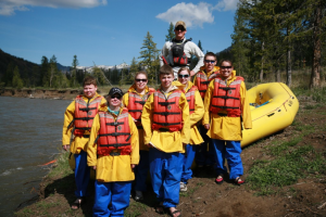 A group of rafters stand next to an inflatable boat on the shore of the Shoshone River in Cody/Yellowstone Country.