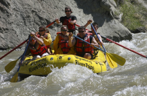 A group of paddlers travel down a river in an inflatable raft in Cody/Yellowstone Country.