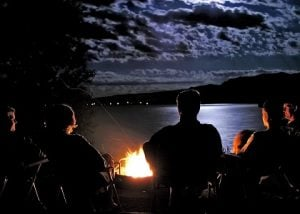 Campers sit around a campfire under the light of the moon in Cody/Yellowstone Country.