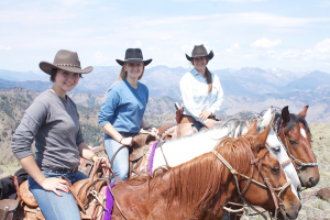 Three riders sit on horseback overlooking mountains in Cody/Yellowstone Country.