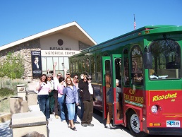 Visitors board the sightseeing trolley in front of the Buffalo Bill Center of the West.