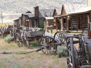 Antique carts and wagons sit outside authentic buildings at Old Trail Town.