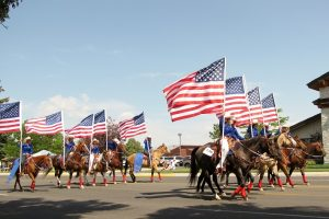 Horseback riders carry American flags in the Cody Stampede Parade.