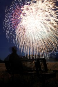 A man sits on a park bench watching the 4th of July fireworks display in Cody, Wyoming.