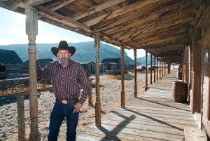 Creator Bob Edger stands on the porch of an historic building in Old Trail Town.