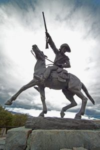 A statue of town founder Buffalo Bill Cody on horseback holding a rifle.