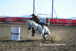 A woman races a horse around a barrel during a rodeo competition.