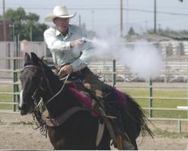 A mounted cowboy shooting a pistol.