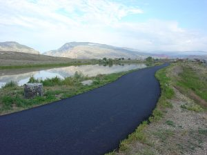 A paved cycling path runs along the water in Beck Lake Park.