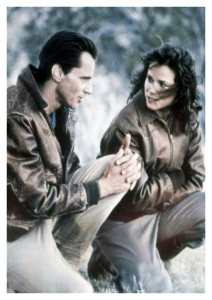 Actors Sam Shepard and Barbara Hershey kneel on the ground on the set of The Right Stuff.