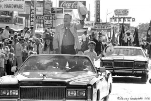 John Wayne stands in the back of a Cadillac and waves at a crowd while serving as the Grand Marshal of the Cody Stampede in 1976.