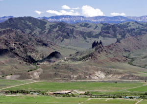 The Absaroka Mountain Range in the distance with green fields in the foreground on a sunny day