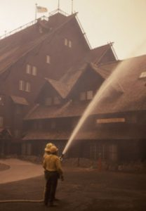 A firefighter sprays water on the Old Faithful Inn to protect the structure from fire.