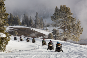 Snowmobiles travel along a winter path