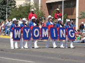 "A group of people marching in a parade hold a sign that says ""Wyoming"""