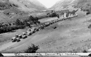 A black and white photo of vehicles making their way along the road in a valley
