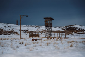 A guard tower on a winter day surrounded by hills