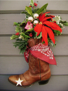A cowboy boot decorated for Christmas with holly and stars