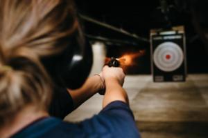 A woman fires a gun at a target
