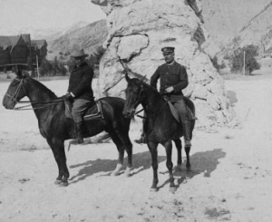 President Roosevelt and Major John Pitcher pose on horseback in front of the Liberty Cap in Yellowstone National Park