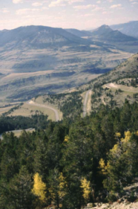 The Chief Joseph Scenic Byway winds down into a valley with mountains in the background